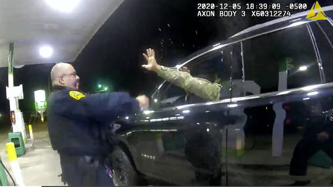 A police officer uses a spray agent on Caron Nazario, who is seated inside his vehicle