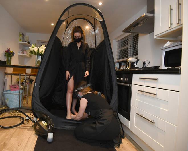 Tan artist Magdelaine Gibson prepares her client Ms Robinson