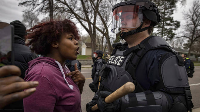 A person confronts a police officer near the site where a family said a man was shot and killed by local law enforcement in Brooklyn Centre, Minnesota