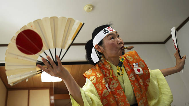 Olympic fan Kyoko Ishikawa shows her cheering at her home in Tokyo