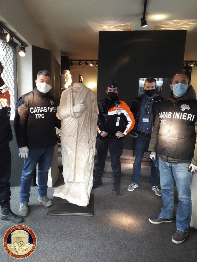 Carabinieri officers of the art squad's archaeological unit pose with a headless Roman statue wearing a draped toga in Brussels