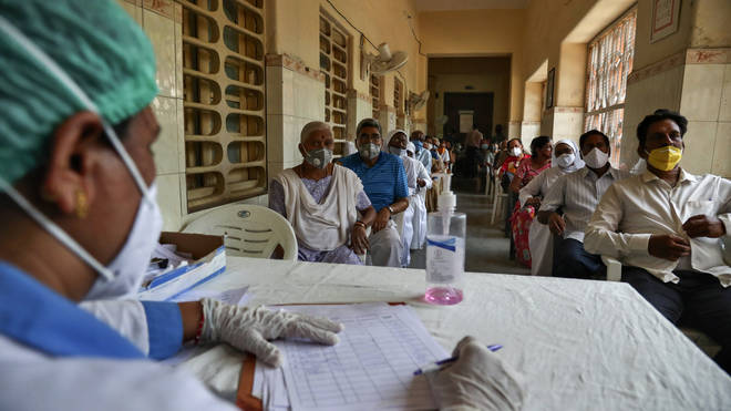 People wait for their turn to be administered Covishield vaccine at a government hospital in Hyderabad, India