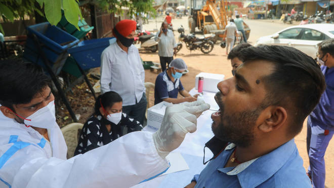 A healthcare worker collects a mouth swab sample from a man at a road side testing centre in New Delhi