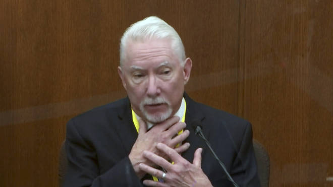 Barry Brodd testifies while placing his right hand across his own throat