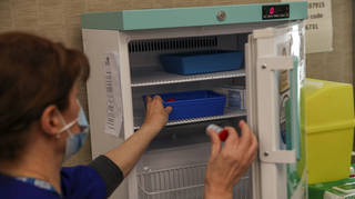 Gwendelina Duquette takes a vial of the Moderna Covid-19 vaccine from the fridge at the vaccination centre at the Madejski Stadium in Reading