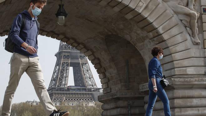 People wearing masks to prevent the spread of Covid-19 cross the Bir Hakeim bridge in Paris (Michel Euler/PA)