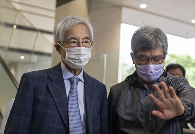 Pro-democracy activist Martin Lee, left, walks out from a court after receiving a suspended sentence