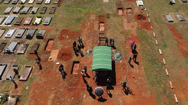 A family attends a burial service in Brasilia, Brazil (Eraldo Perez/AP)