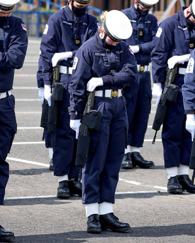 A Royal Navy rating bows her head