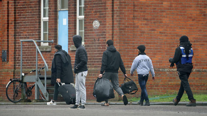 Two men leave Napier Barracks in Folkestone, Kent, which is currently being used by the government to house people seeking asylum in the UK