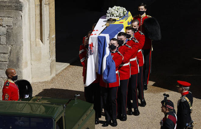 Members of the Queen's Company, 1st Battalion Grenadier Guards prepare to place the coffin onto the Land Rover