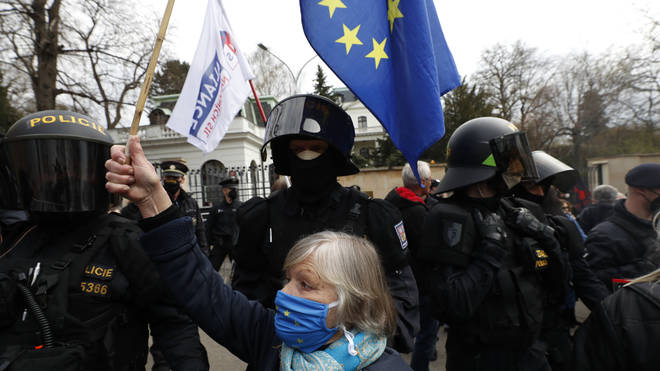 A woman waves a European Union flag in front of the Russian embassy in Prague, Czech Republic