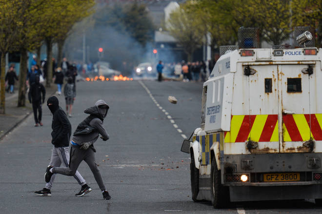 Rioters hurled objects at police vehicles as furniture burned on the street