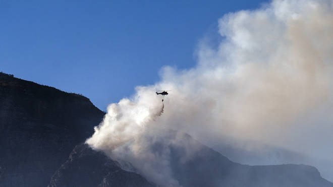 A South African military helicopter drops water on the top of Table Mountain in Cape Town