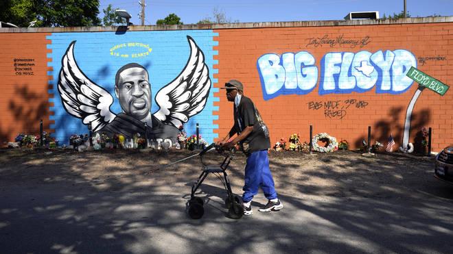 A man walks past a mural in the Houston neighbourhood where George Floyd grew up