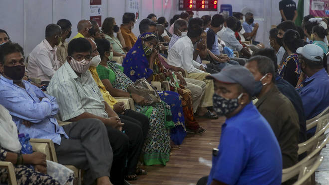 People wait to receive a vaccine in Mumbai, India