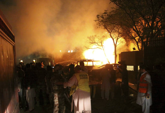 A police officer and rescue workers arrive at the site of bomb blast in Quetta