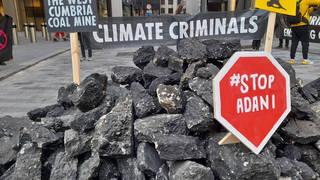 Extinction Rebellion activists have tipped 'coal' outside Lloyds of London insurance market
