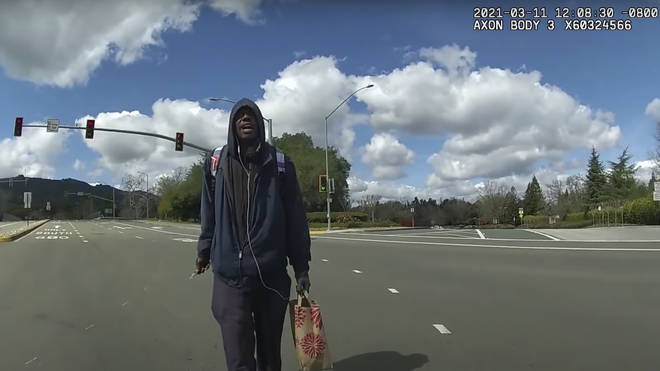 This image from body-worn camera video provided by the Contra Costa Sheriff shows Tyrell Wilson, holding a knife in his right hand, approaching Deputy Andrew Hall in the middle of an intersection on March 11 2021 in Danville, California