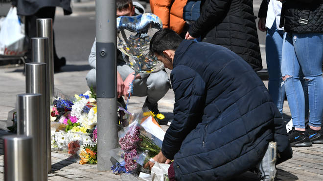 People place flowers at the scene in Barking Road, East Ham, where 14-year-old Fares Maatou was knifed to death