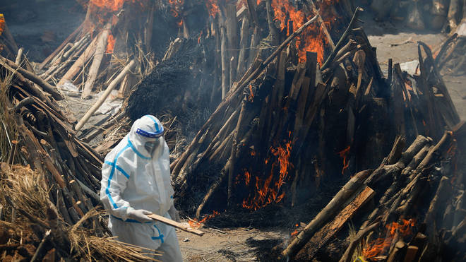A man wearing PPE walks through burning pyres of people who have died from Covid-19