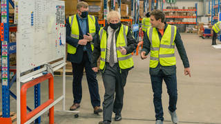 Boris Johnson walks in the warehouse of Next World Sports during his visit to Wrexham