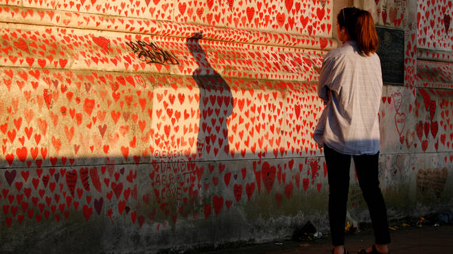A woman looks at the National Covid Memorial Wall of hearts, each heart representing an individual coronavirus death, in evening sunlight in London