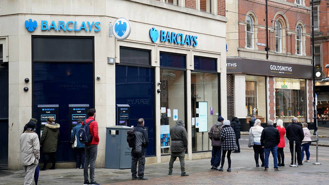 Customers queue outside a Barclays bank