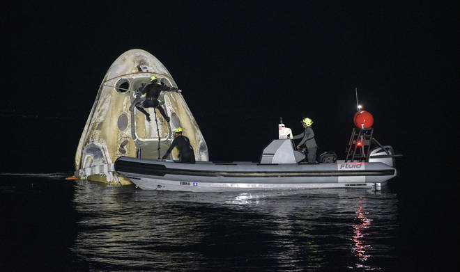 Support teams work around the SpaceX Crew Dragon Resilience spacecraft shortly after it landed.
