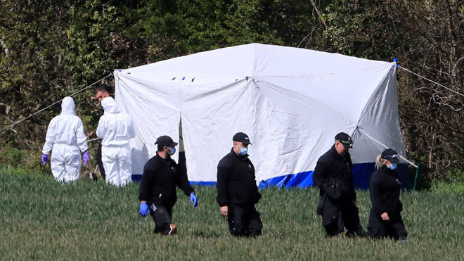 Police forensic officers near the scene at Akholt Wood, close to the hamlet of Snowdown.