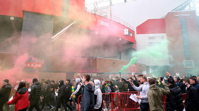 Fans break through the barriers outside Old Trafford before storming the stadium