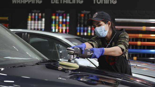 Iranian car detailer Maryam Roohani polishes a car at a detailing shop in Tehran