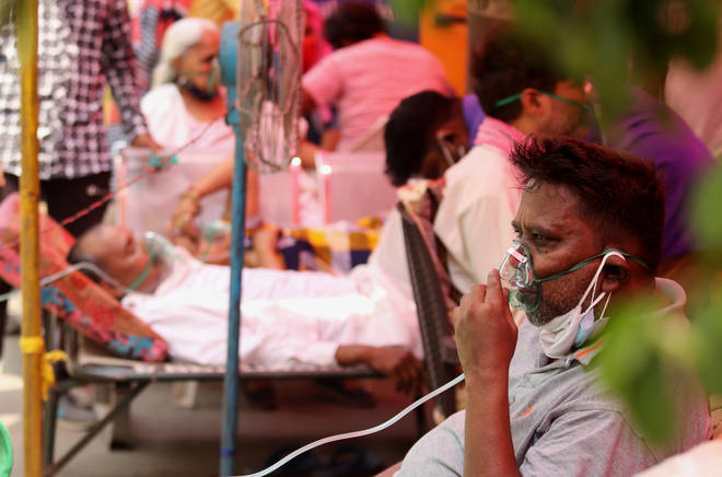 Covid-19 patients suffering from breathing difficulty breath with the help of oxygen masks outside Gurudwara