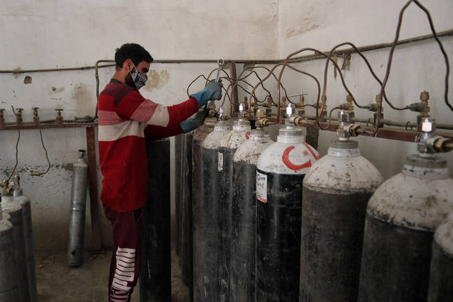A worker refills oxygen cylinders at a facility as demands rise in the hopitals in Srinagar
