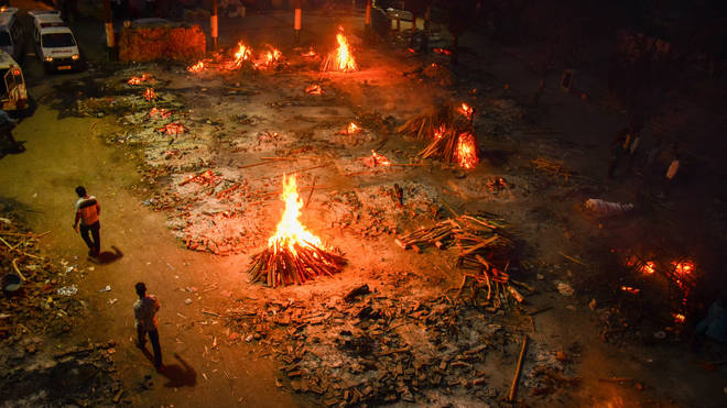 Funeral pyres of people who have died of Covid-19 burn during a mass cremation at a crematorium