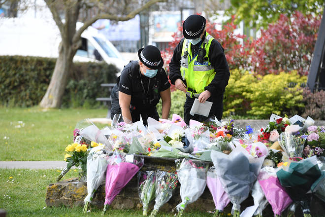 Two police officers lay floral tributes in a park in Aylesham village close to where Ms James was found