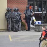 Officers stand near an entrance to the Wells Fargo branch