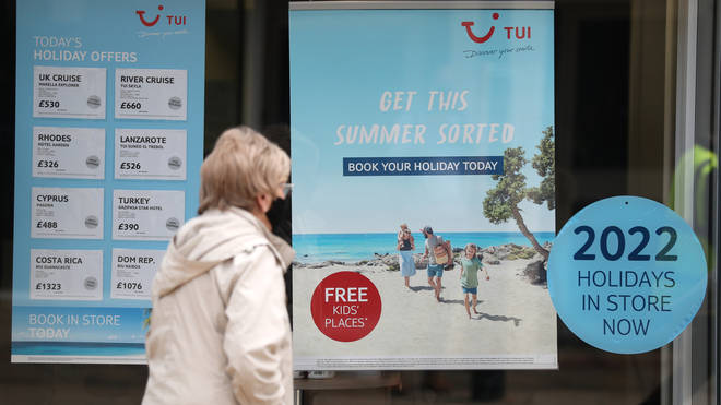 A person makes their way past the shop window of a Tui store in Hampshire