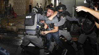 Israeli police wrestle a Palestinian man