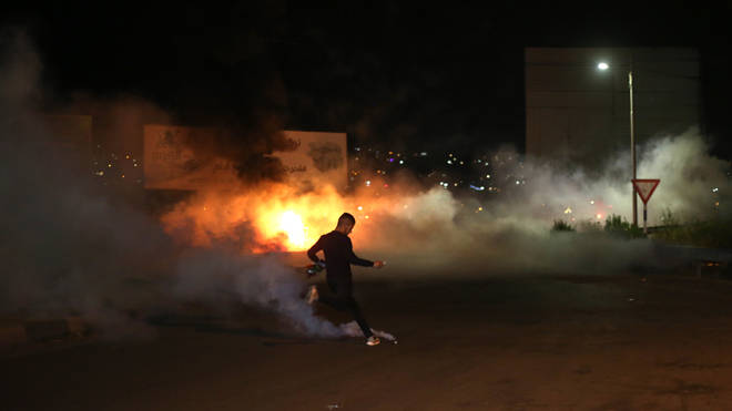A Palestinian protester kicks back a tear gas canister during clashes with Israeli soldiers following an anti-Israel protest