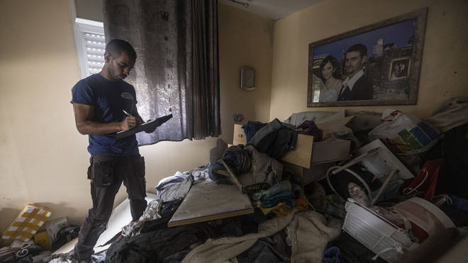 Israeli officials inspect an apartment block destroyed by Hamas rockets