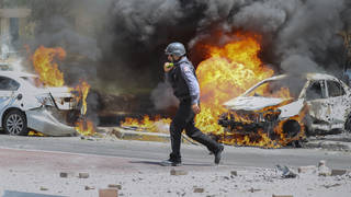 An Israeli firefighter walks next to cars hit by a missile fired from the Gaza Strip in the southern Israeli city of Ashkelon