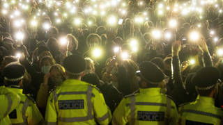 People in the crowd turn on their phone torches as they gather in Clapham Common on March 13