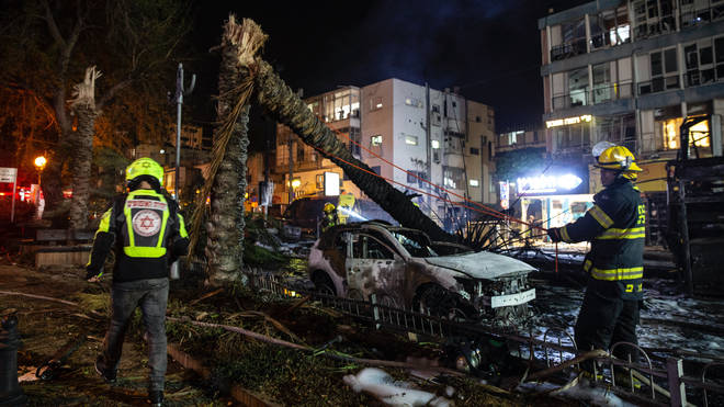 An Israeli firefighter works at the site where a rocket, fired from the Gaza, hit the central Israeli town of Holon, near Tel Aviv