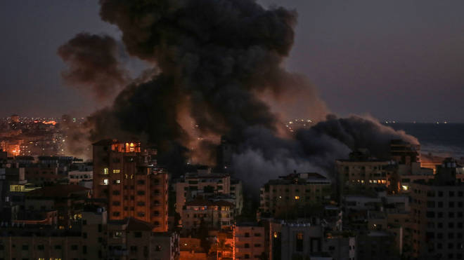 Thick smoke billows from Hanadi residential tower in Gaza after it was hit by an Israeli airstrike