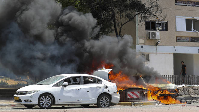 Cars burn after being hit by a missile fired from the Gaza Strip in the southern Israeli town of Ashkelon