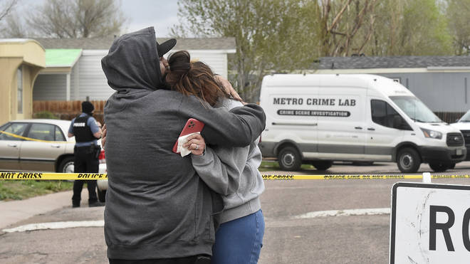 Freddy Marquez kisses the head of his wife, Nubia Marquez, near the scene of a fatal shooting which has been marked off with police tape