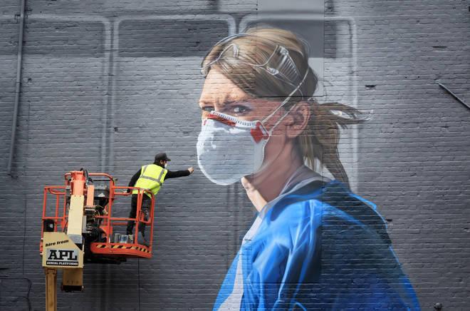 Artist Peter Barber working on a mural in Manchester city centre, depicting nurse Melanie Senior