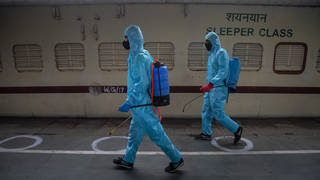 Health workers in personal protective equipment sanitise a train prepared as a Covid-19 care centre at a railway station in Gauhati, India