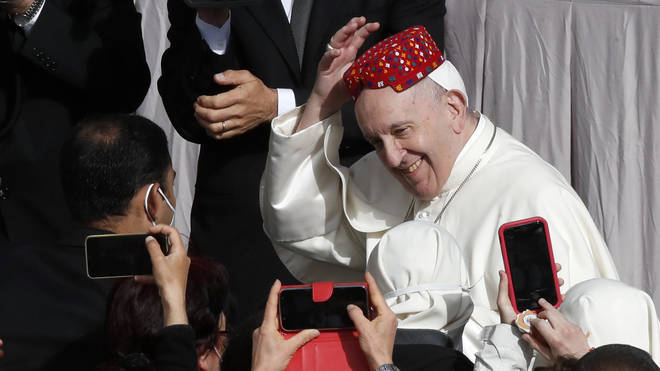 Pope Francis smiles after an attendee placed a hat on his head in the St Damaso Courtyard at the Vatican for his weekly general audience